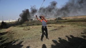 Palestyński protestant rzucający kamieniem.